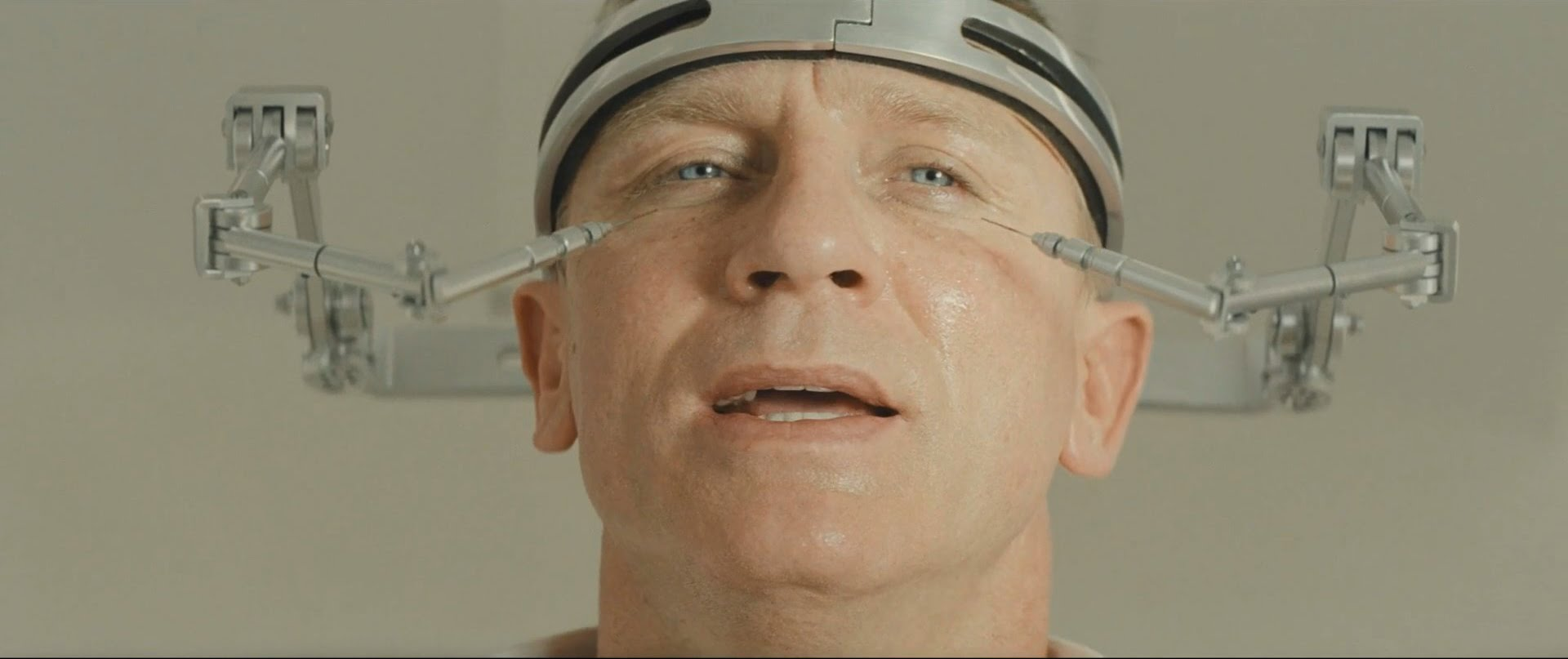 A scene from a James Bond movie; Daniel Craig pictured with a device on his head
