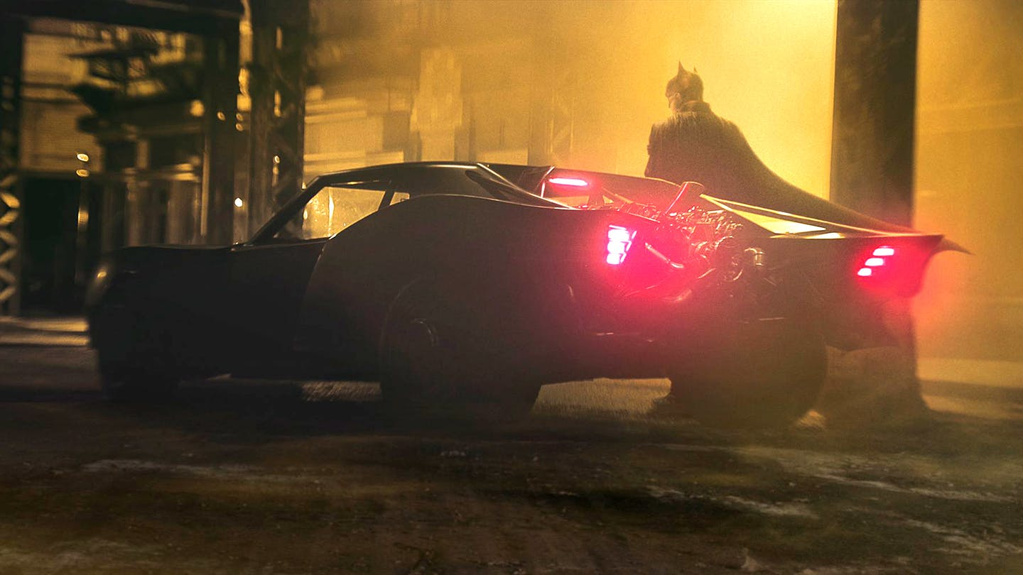 The back of a black sports car shot during the night with a glimpse of Batman behind it