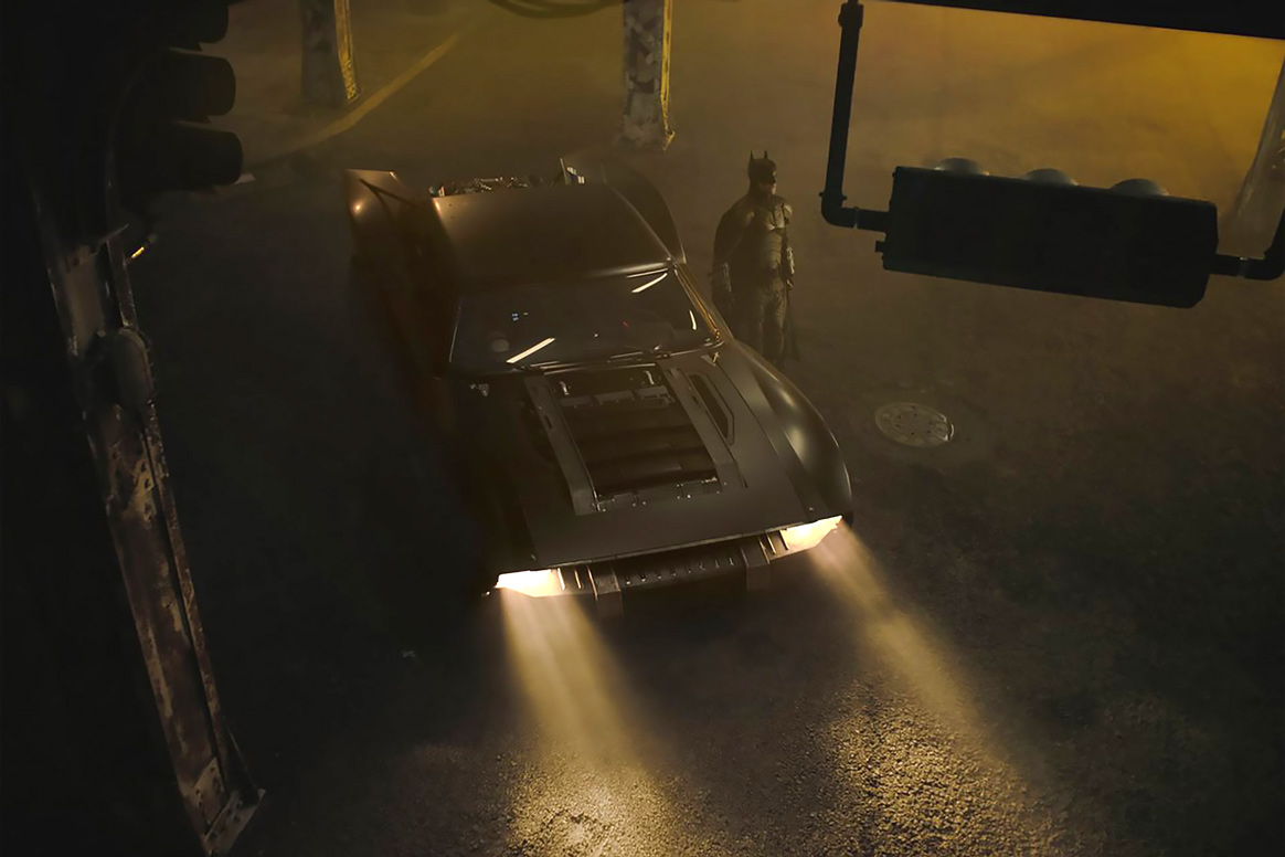 Dimly-lit picture of Batman standing next to his Batmobile
