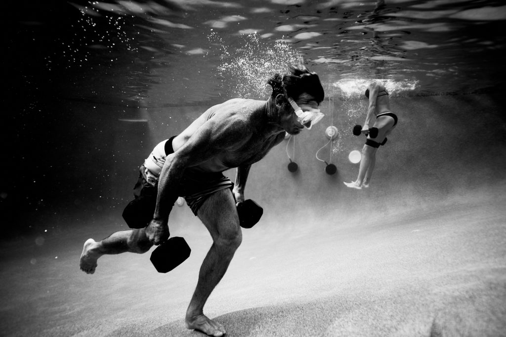 Scott Carney running underwater while carrying dumbbells