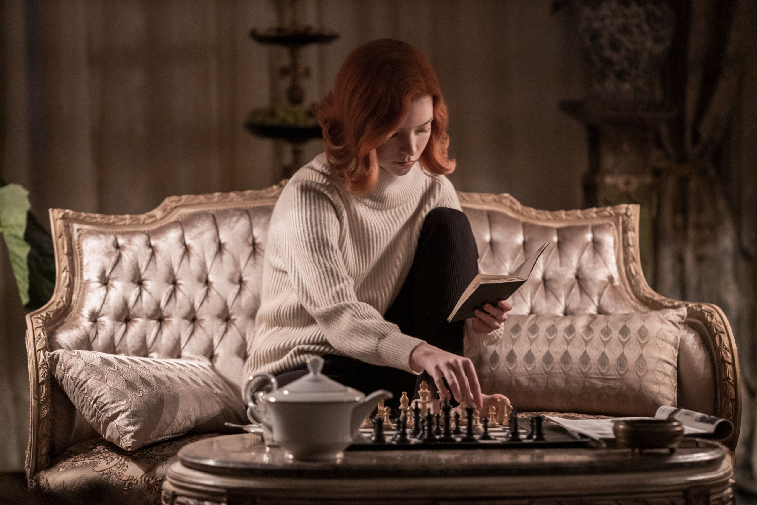 Beth reading a book, practicing on her chess board at home