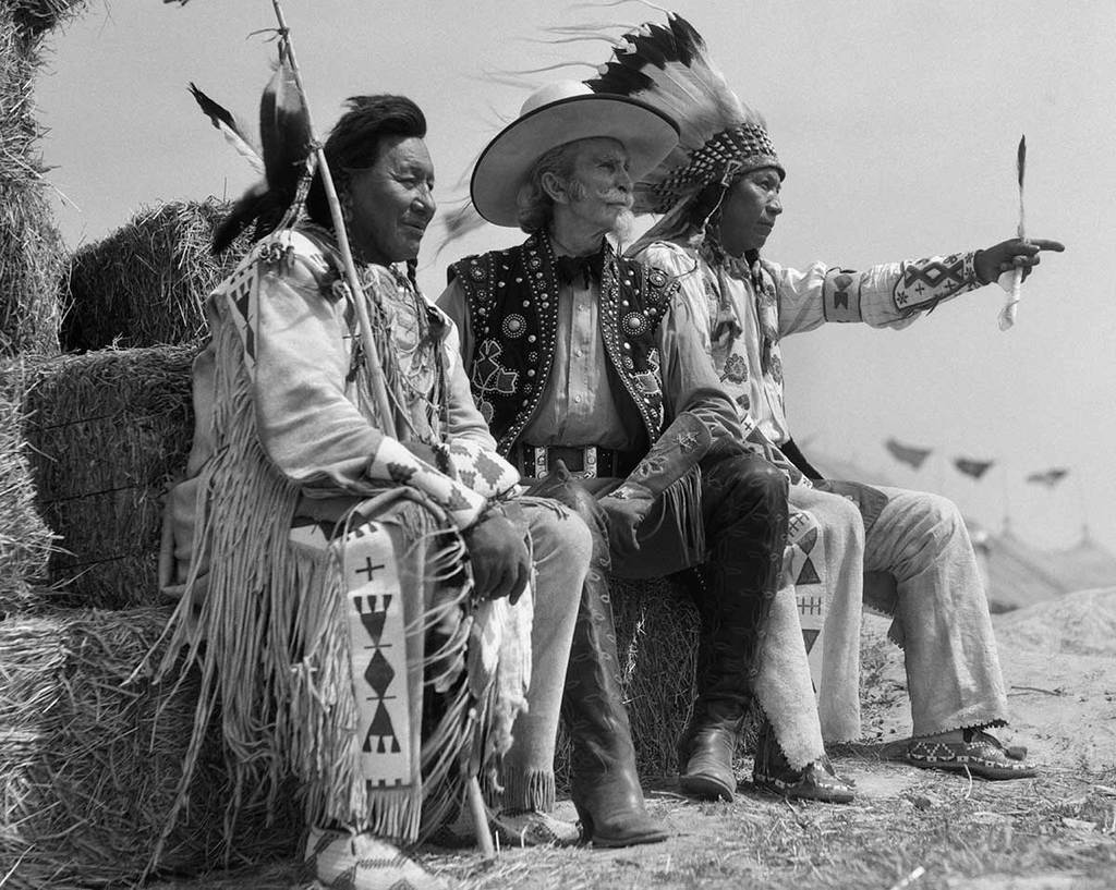 A cowboy sits alongside two Native American men who seem to be looking at something interesting off in the distance