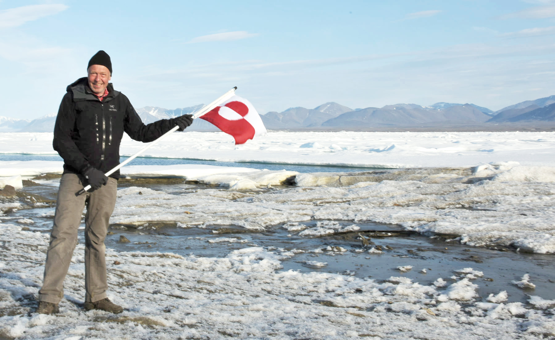 Morten Rasch posing with the flag of Greenland during an arctic expedition.